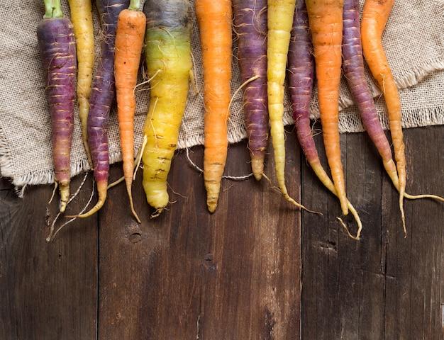Frische organische regenbogen-karotten auf einer hölzernen tischoberansicht