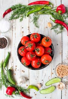 Frische organische rote tomaten im schwarzblech auf weißem holztisch mit den grünen und rot- und paprikapfeffern, grünen paprikas, schwarzen pfefferkörnern, salz, abschluss oben, gesundes konzept