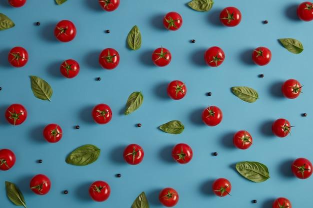 Frische organische rote tomaten, pfefferkörner und basilikumblätter auf blauem hintergrund. gemüse für die zubereitung von salat geerntet. gesundes essen und vitaminkonzept. horizontale aufnahme, draufsicht. leckeres natürliches essen
