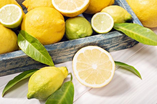 Frische organische zitrone trägt mit blättern auf holztisch früchte
