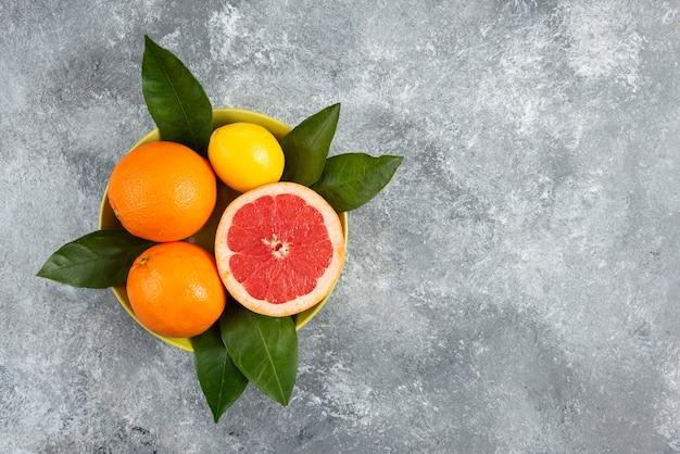 Frische organische zitrusfrüchte in schüssel mit blättern über grauem tisch.