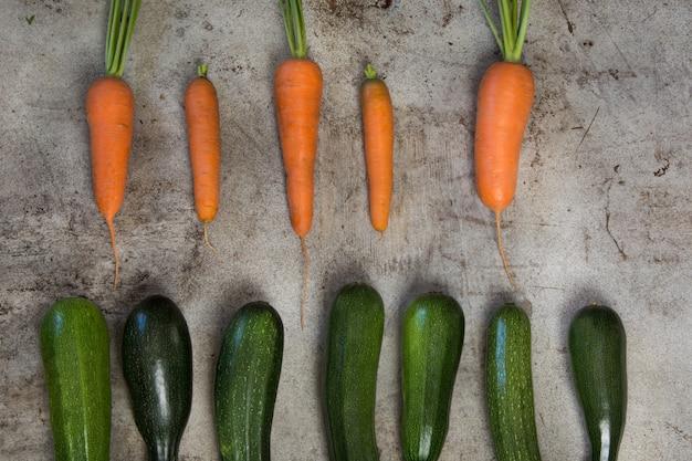 Frische organische zucchini und karotte auf rustikaler tabelle