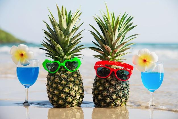 Frische paarananas mit sonnenbrillen und cocktailgläsern auf sauberem sand setzen mit seewelle - frische frucht und getränk mit meersandsonnen-ferienkonzept auf den strand