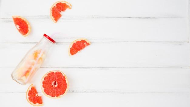 Frische pampelmusen und orangen in der nähe von flasche