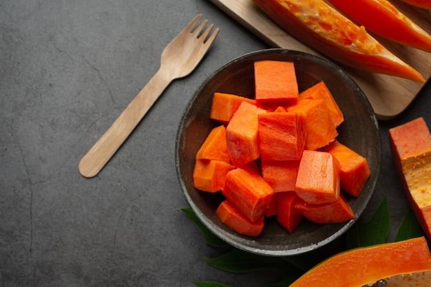 Frische papaya, in stücke geschnitten, auf einen schwarzen teller legen.