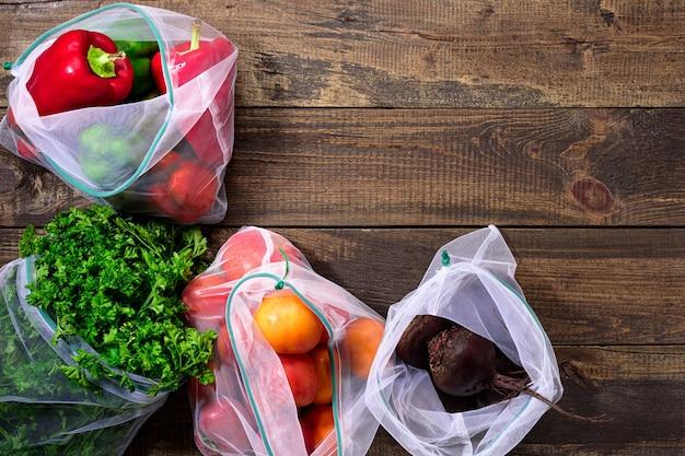Frische paprika, tomaten, rüben und gemüse in wiederverwendbaren umweltfreundlichen beuteln auf hölzernem braunem hintergrund mit kopienraum