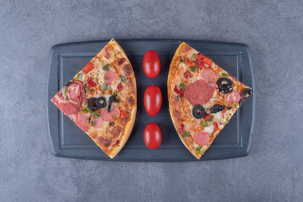 Frische peperoni-pizzastücke auf holzbrett.