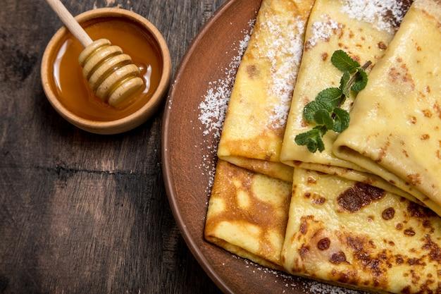 Frische pfannkuchen mit wohlriechendem ahornsirup und honig. russische feiertagspfannkuchenwoche. crepes mit honig oder sirup