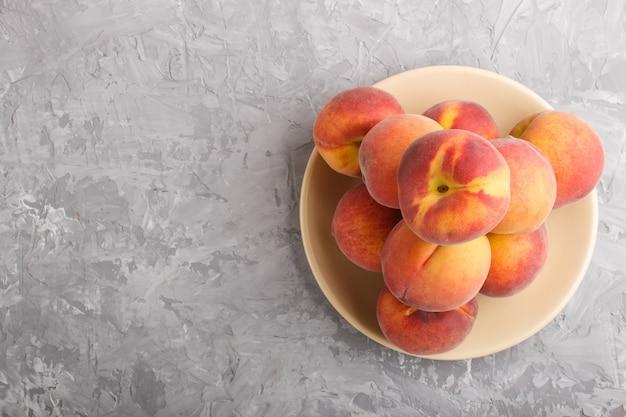 Frische pfirsiche auf einer platte auf grauem konkretem hintergrund. ansicht von oben.