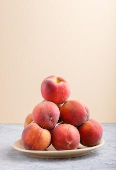 Frische pfirsiche auf einer platte auf grauem und orange pastellhintergrund. seitenansicht.