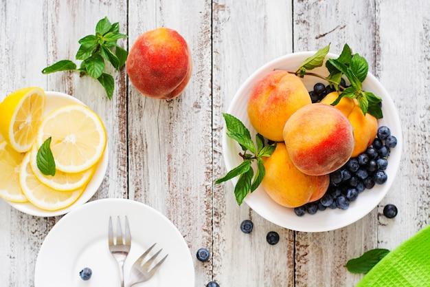 Frische pfirsiche und blaubeeren in der schüssel holz im rustikalen stil. draufsicht