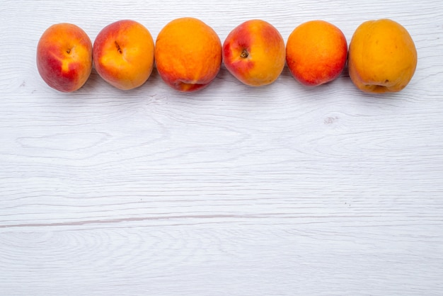 Frische pfirsiche von oben und weich auf der weißen hintergrundfruchtfarbe frisch