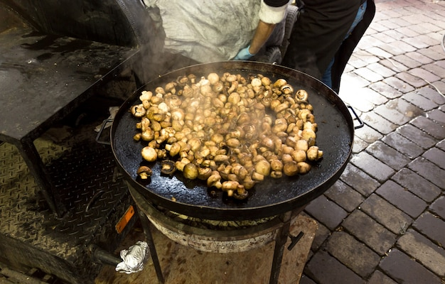 Frische pilze, die in einer großen metallpfanne im freien braten