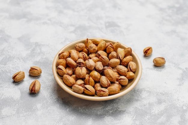 Frische pistazien in den keramischen platten beschneidungspfad eingeschlossen