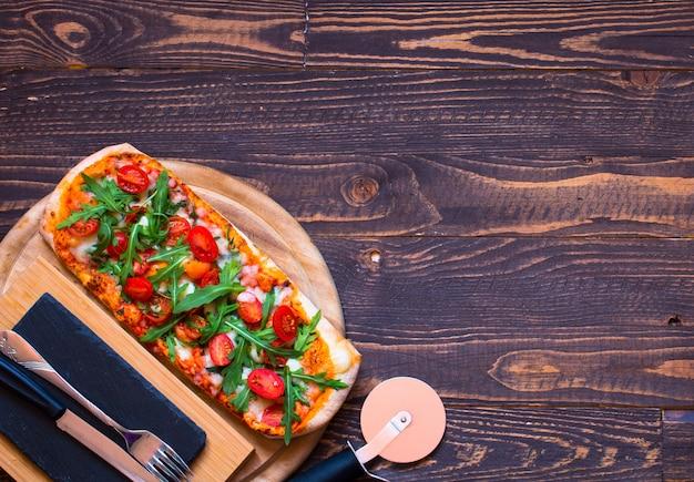 Frische pizza des hausmädchens mit tomaten rucola und mozzarell