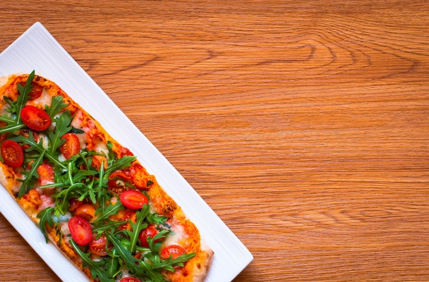 Frische pizza des hausmädchens mit tomaten, rucola und mozzarell