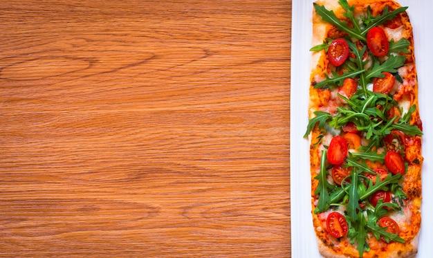 Frische pizza des hausmädchens mit tomaten, rucola und mozzarella
