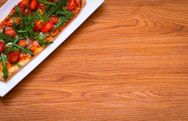 Frische pizza des hausmädchens mit tomaten, rucola und mozzarellaahintergrund