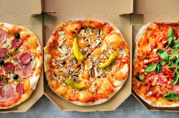 Frische pizza im lieferungskasten auf grauem konkretem hintergrund. draufsicht, raum kopieren