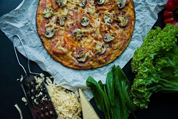Frische pizza mit wurst, tomaten, pilzen und käse auf einer dunklen oberfläche