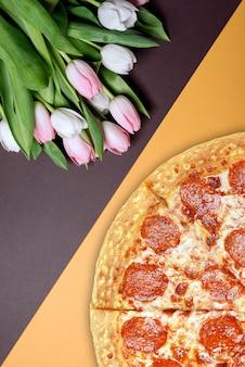 Frische pizza und frühlingsblumen tulpen.