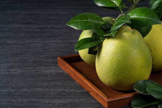 Frische pomelo auf schwarzem schieferhintergrund für mid-autumn festival-frucht.