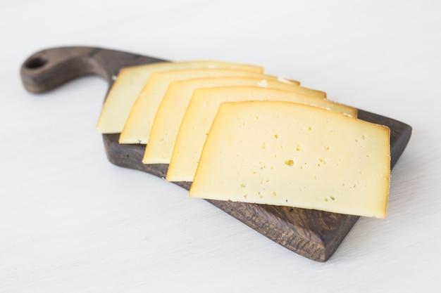 Frische produkte geschnittenen käse auf rustikalem tisch