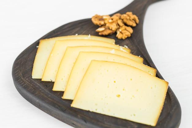 Frische produkte. geschnittener käse auf rustikalem tisch.