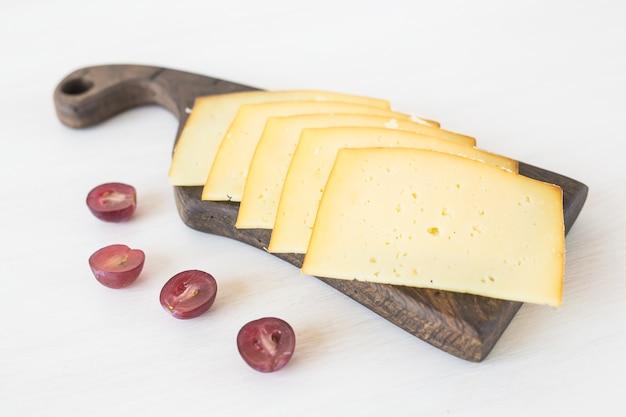 Frische produkte. geschnittener käse mit trauben auf rustikalem tisch.