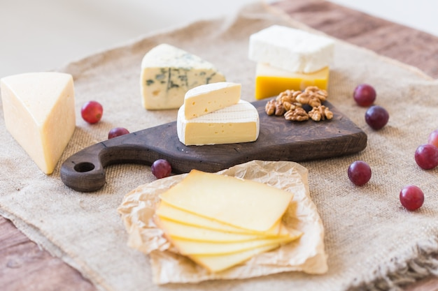 Frische produkte käse brie camembert trauben und nüsse auf rustikalem tisch
