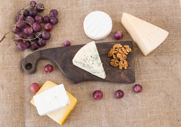Frische produkte. käse, brie, camembert, trauben und nüsse auf rustikalem tisch.