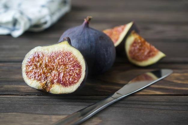 Frische purpurrote feigenfrüchte und -scheiben auf holztisch mit messer und serviette
