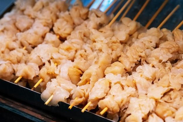 Frische quallen auf hölzerner aufsteckspindel für grill grillten, thailändischer straßenlebensmittelmarkt