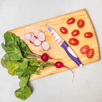 Frische radieschen und tomaten auf hölzernem schneidebrett