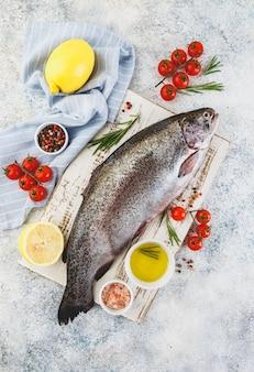 Frische regenbogen rohe forelle mit kräutern rosmarin, tomaten, pfefferkörnern, olivenöl, himalaya-salz und zitrone auf weiß.