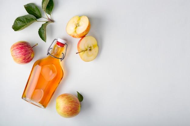 Frische reife äpfel und apfelessig. apfelwein in einer glasflasche und frische äpfel. heller hintergrund. draufsicht. kopieren sie den speicherplatz ihres textes.