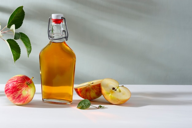 Frische reife äpfel und apfelessig. apfelwein in einer glasflasche und frische äpfel. heller hintergrund.