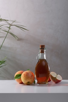 Frische reife äpfel und apfelessig auf dem tisch. heller hintergrund.