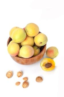 Frische reife aprikosen in der holzschale isoliert
