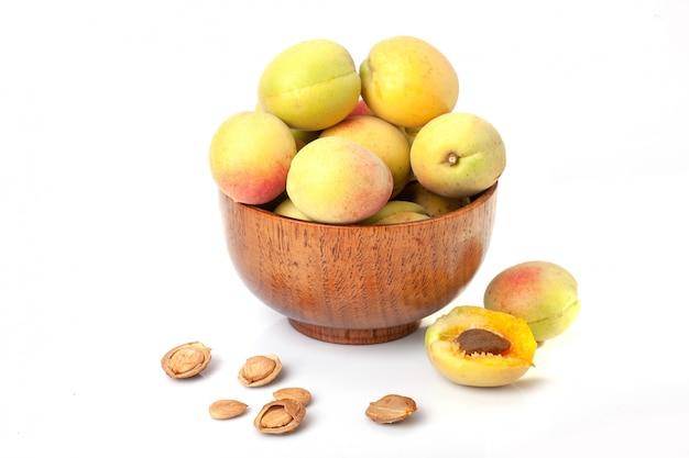 Frische reife aprikosen in der holzschale lokalisiert auf einem weißen hintergrund.