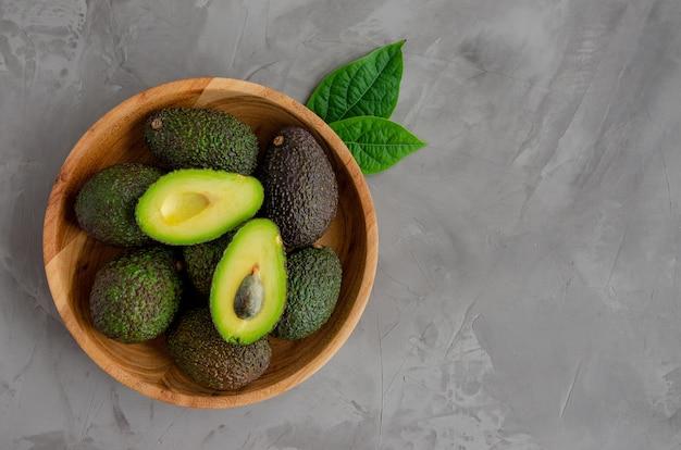 Frische reife avocado mit blättern in einem holzteller