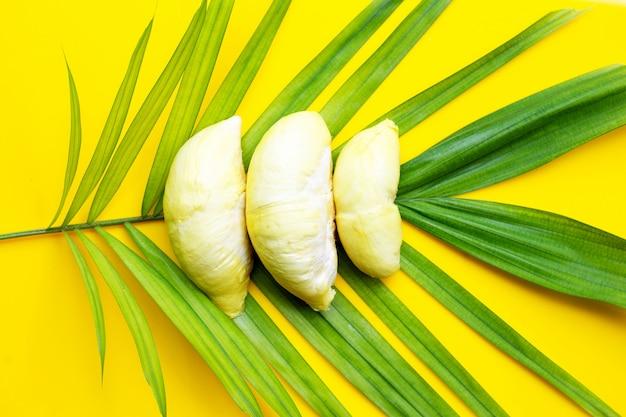 Frische reife durian auf tropischen palmblättern auf gelber oberfläche