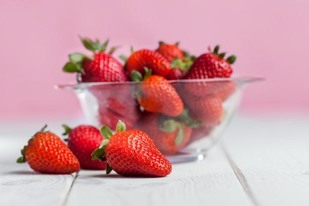 Frische reife erdbeere in der glasschale auf holz