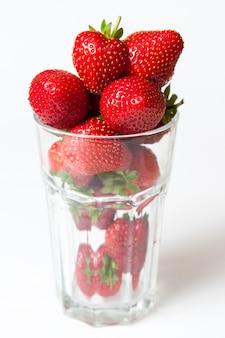 Frische reife erdbeere in einem glas lokalisiert