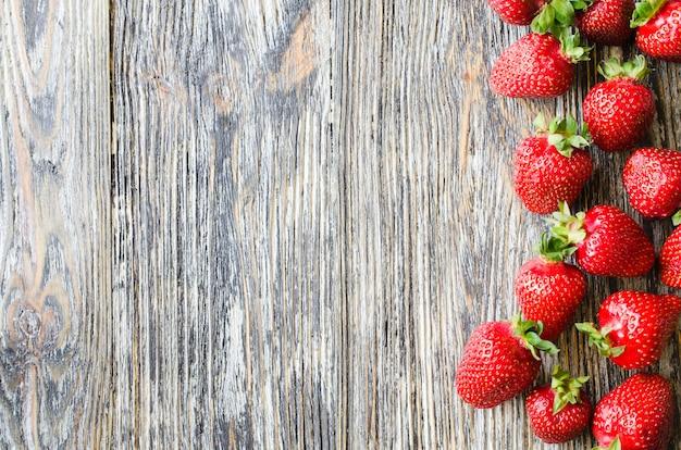 Frische reife erdbeeren auf einem hölzernen hintergrund. bio saftige beeren.