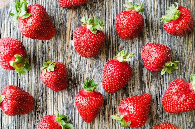 Frische reife erdbeeren auf einem holztisch. bio saftige beeren.