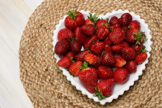 Frische reife erdbeeren auf einer herzweissen platte mit einem jute-tisch