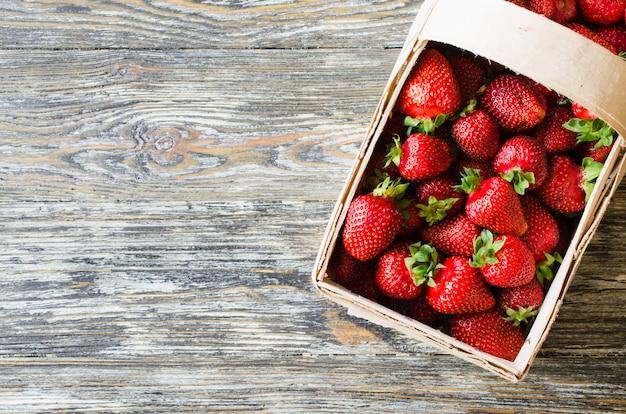 Frische reife erdbeeren in einem hölzernen korb auf einem hölzernen hintergrund. bio saftige beeren.