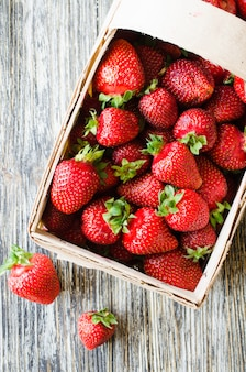 Frische reife erdbeeren in einem holzkorb auf einem holztisch. bio saftige beeren.