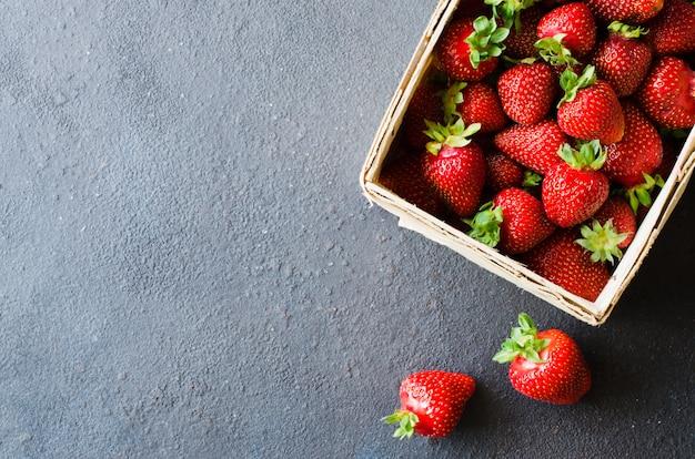 Frische reife erdbeeren in einem holzkorb. bio saftige beeren.